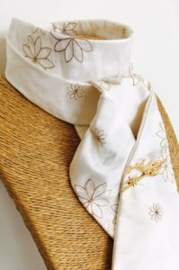 White embroidered honey toned silk stock pre tied with gold horse's head stock pin